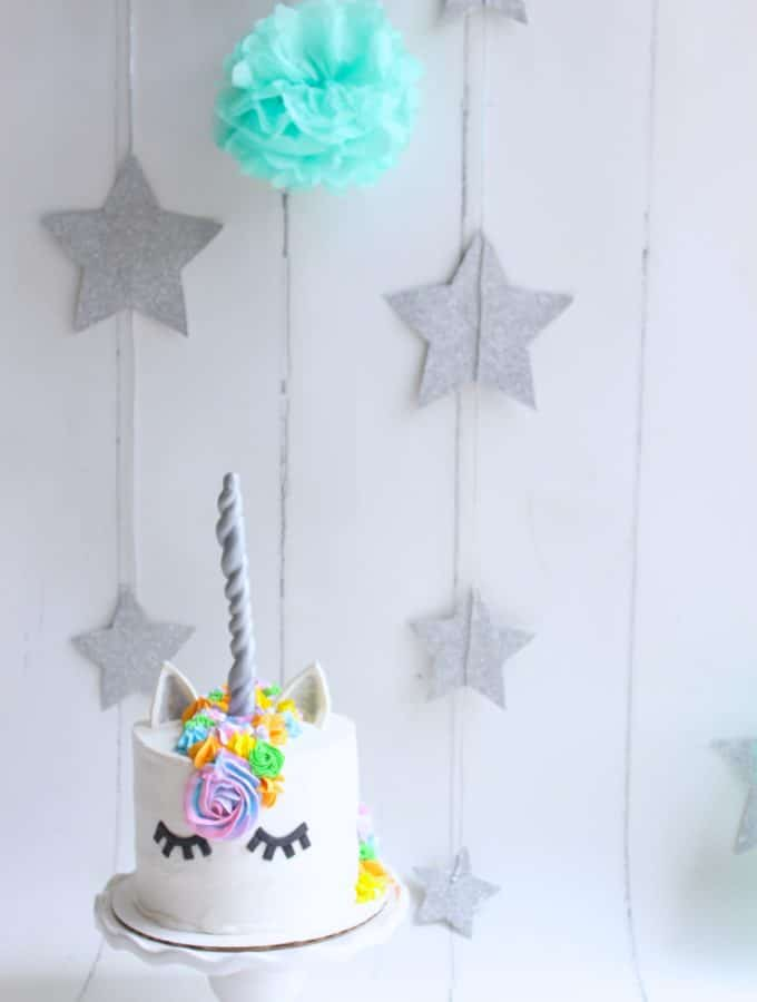 A white cake decorate to look like a unicorn on a white backdrop with sparkly stars hanging in the back