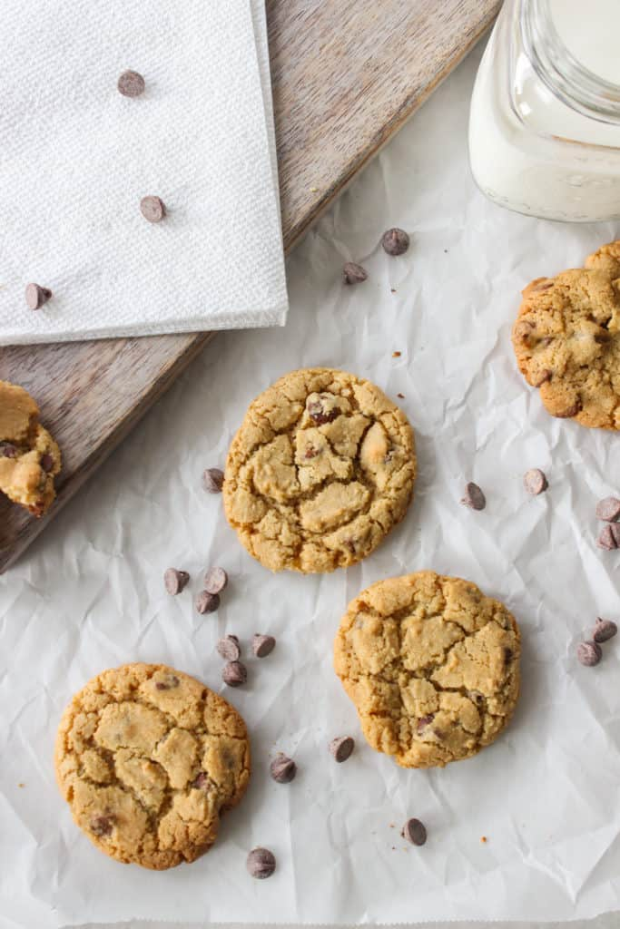 chewy chocolate chip cookies on parchment paper scattered with chocolate chips