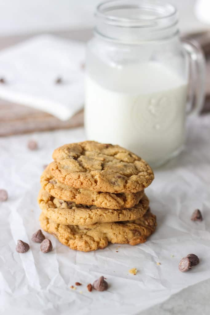 stack of four chewy chocolate chip cookies in front of large glass of milk