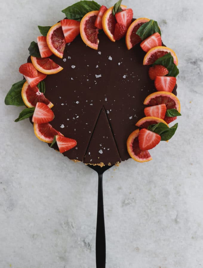 A chocolate tart topped with strawberries, sea salt, and sliced blood oranges