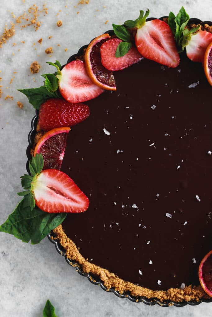 chocolate tart topped with sliced strawberries, sea salt, and sliced blood oranges