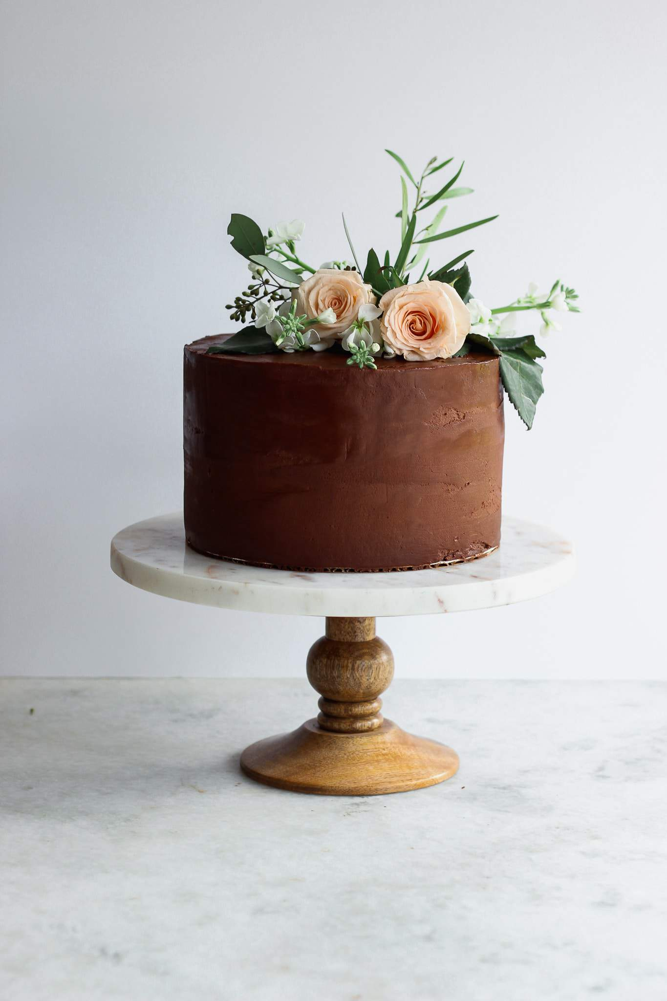 A chocolate cake on a marble and wood cake stand with flower decorations