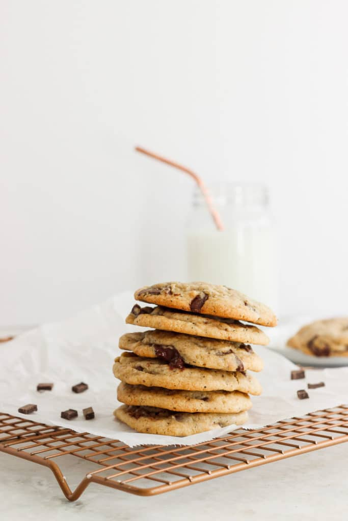 Chocolate coffee cookies stacked on a cooling rack next to a glass of milk