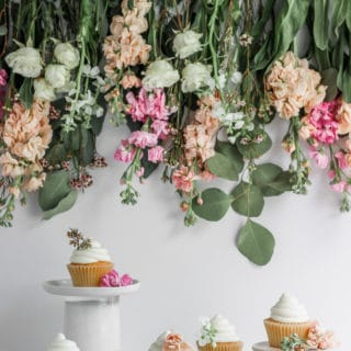 Vanilla cupcakes styled against a flower backdrop.