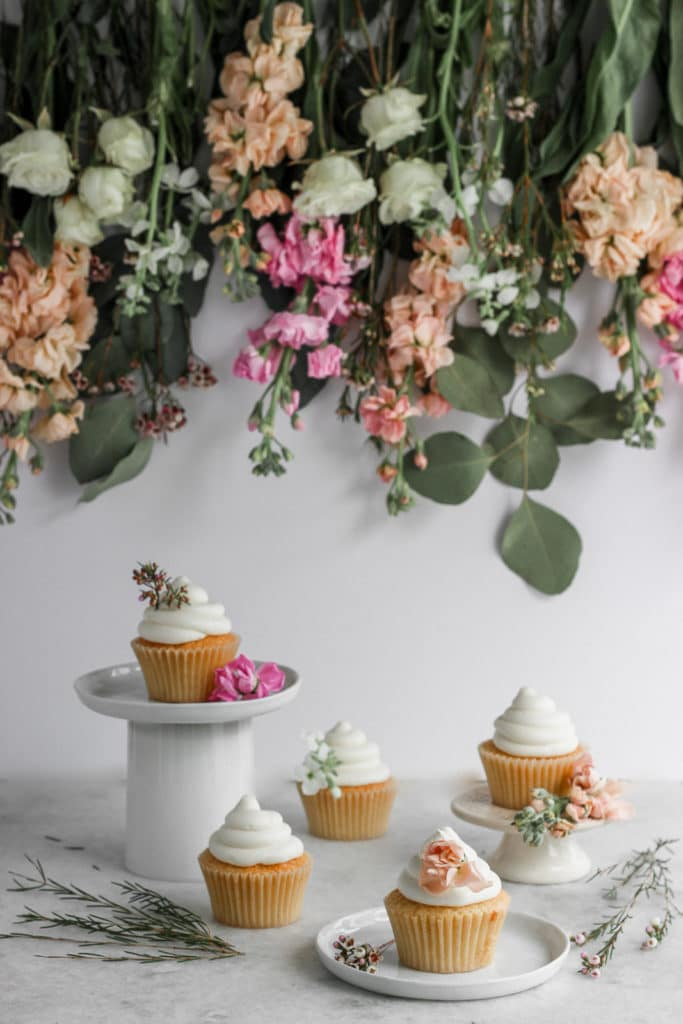 vanilla frosted cupcakes styled on a white background with flowers hanging behind them