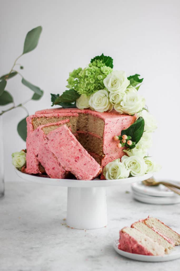 Slices of strawberry basil cake standing up on a white cake stand.
