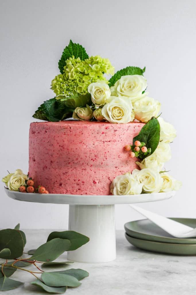A pink strawberry basil cake on a white cake stand decorated with hydrangeas and roses.
