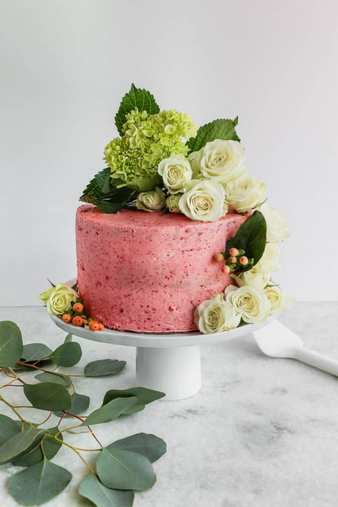 A pink cake decorated with fresh flowers with a tutorial on how to decorate a cake with flowrers