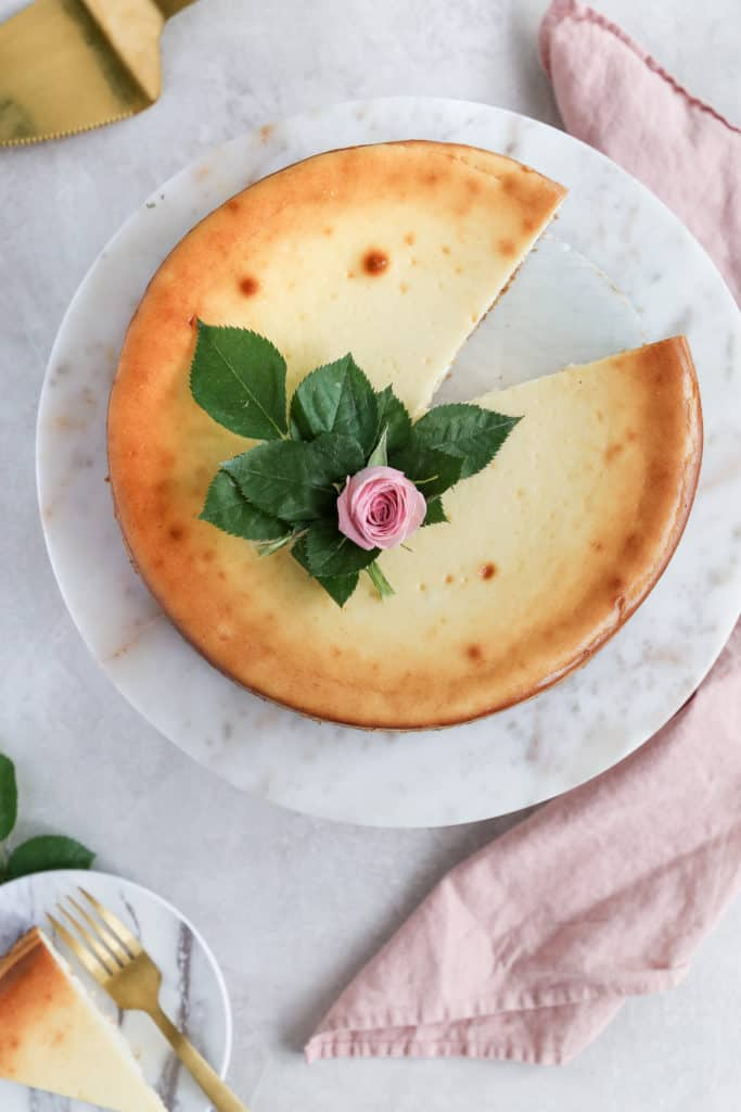 A classic cheesecake with a slice taken out of it decorated with a pink flower.