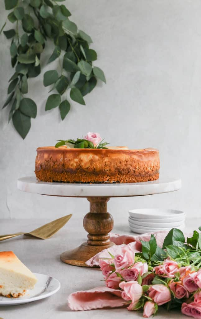 A cheesecake on a marble and wood cake stand decorated with pink flowers