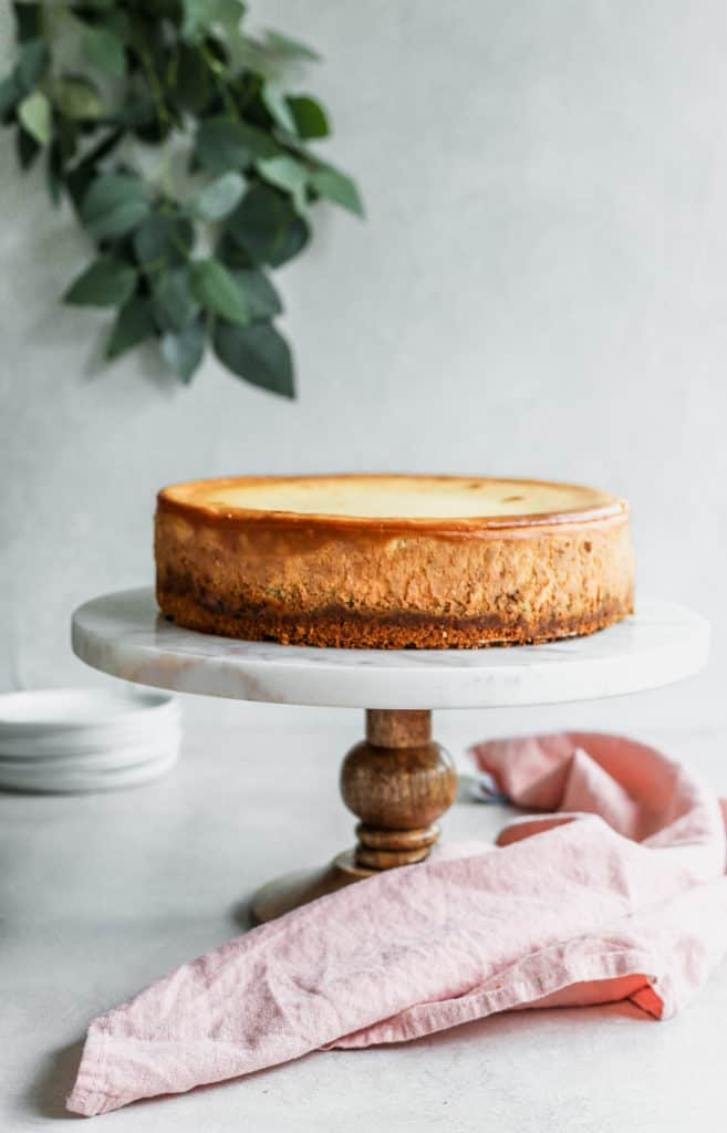A crack free beautiful classic cheesecake in a marble and wood cake stand with a pink napkin