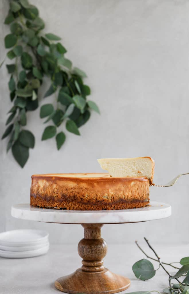 Cheesecake slice being lifted from the cake on a marble and wood cake stand.