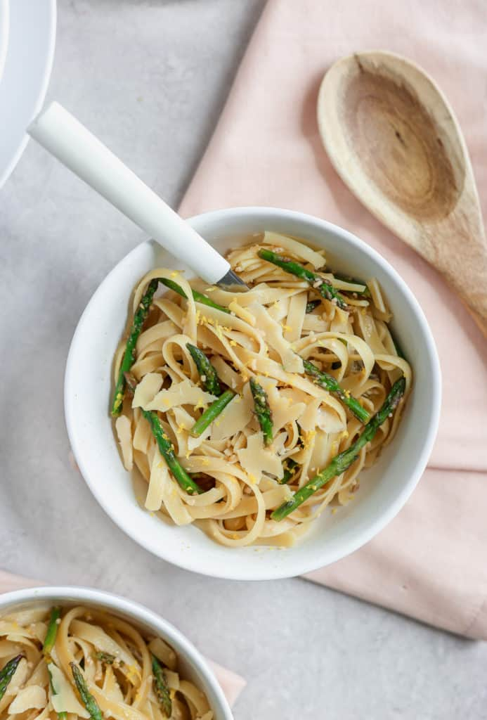 Fettuccine dish with asparagus and lemon served in a white bowl over a pink napkin.