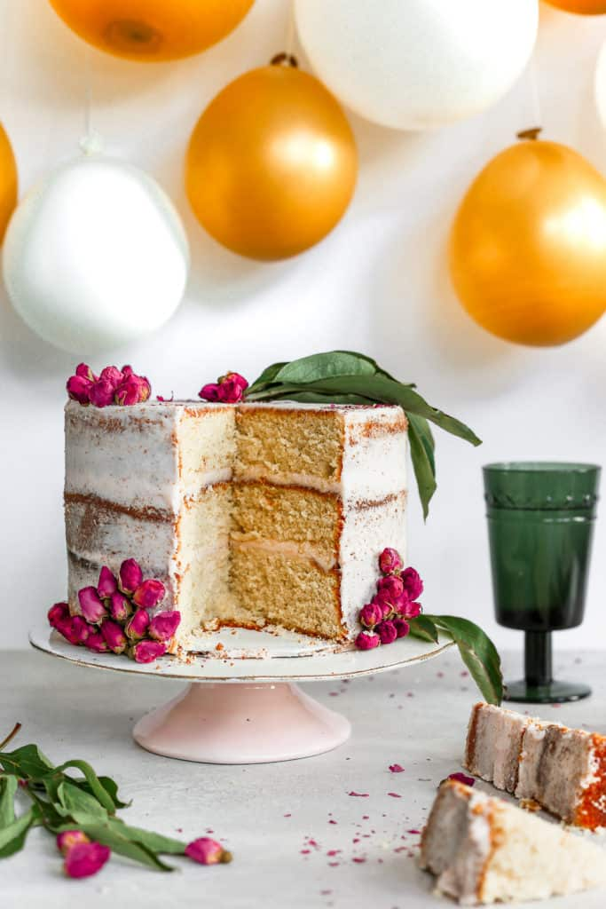 sliced orange cardamom cake garnished with dried rose petals on cake stand in front of balloon backdrop