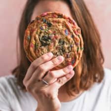 A girl holding a giant cookie up to her face