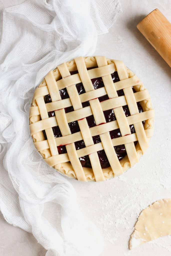 A beautiful picture of a pre baked lattice crust homemade cherry pie.