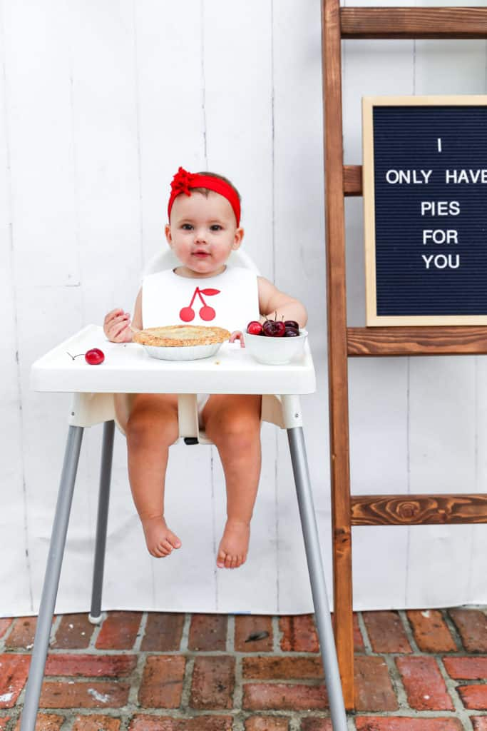 A happy baby girl eating cherry pie in a white high chair