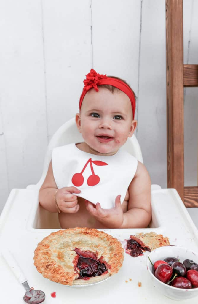 Cute baby wearing a cherry pie bib and eating cherry pie in a highchair
