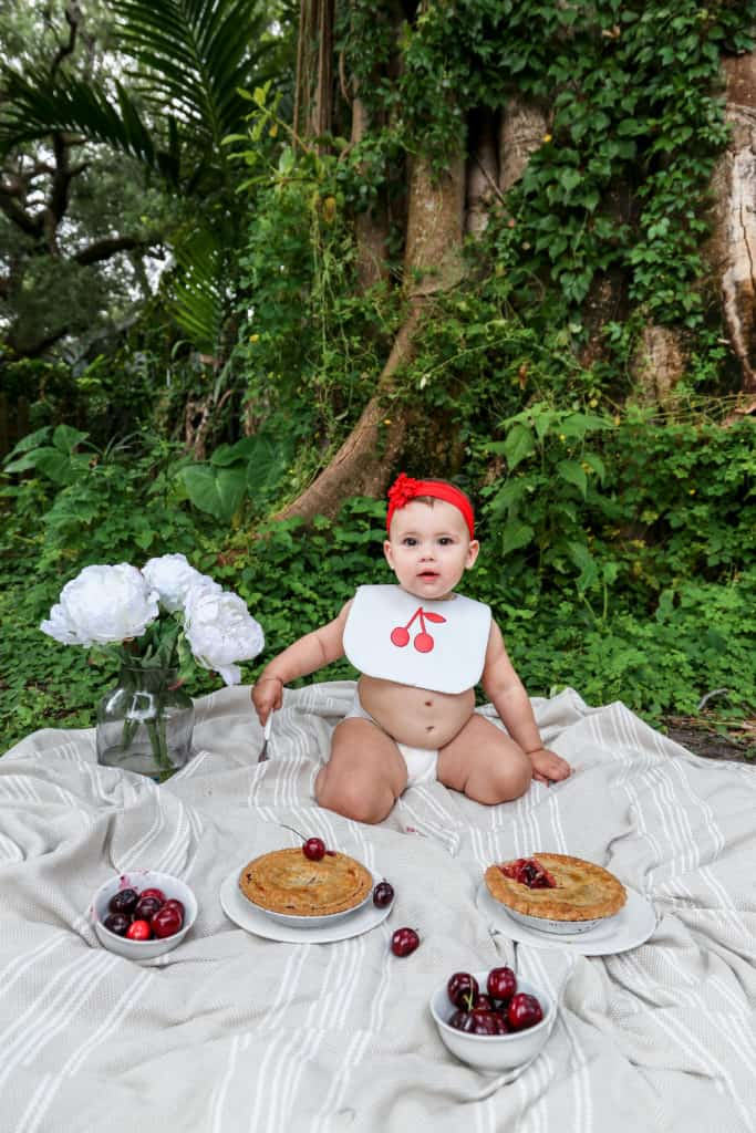 A beautiful baby girl eating cherry pie on a blanket on the grass
