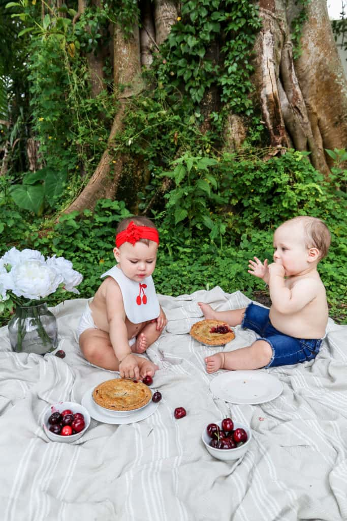 Two cute babies eating cherry pies on a blanket on the grass