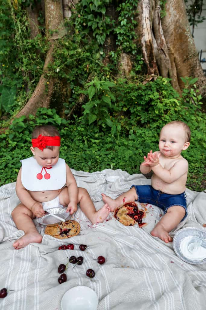 Two cute babies eating pie on the grass