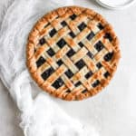 A beautiful picture of a semi homemade cherry pie with lattice crust fresh out of the oven.