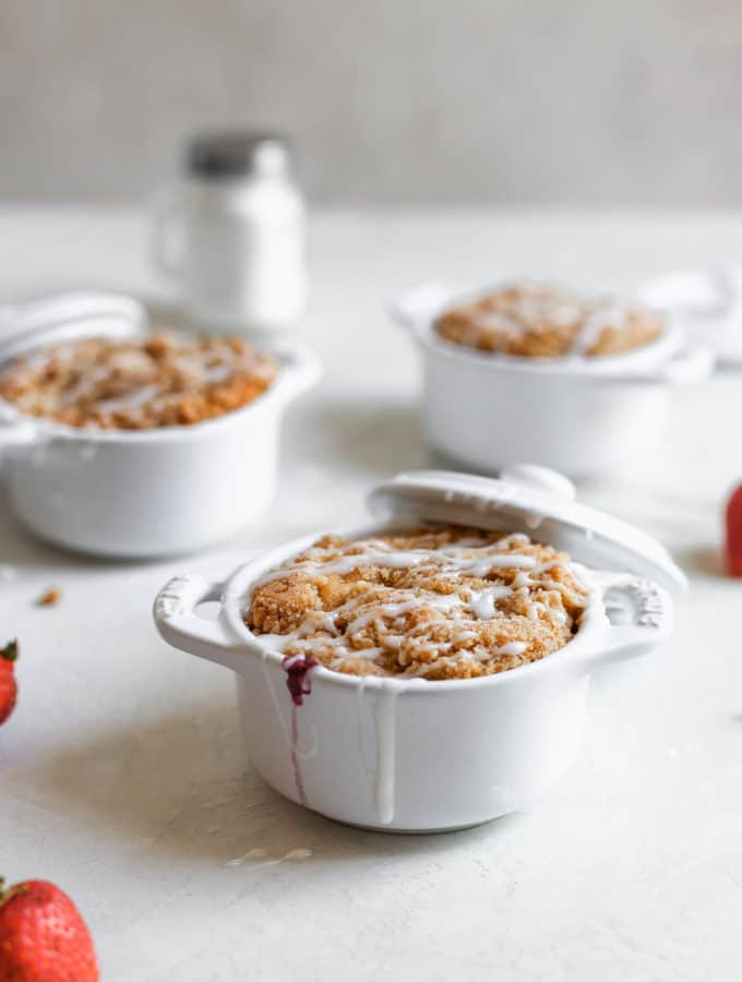 Triple berry coffee cakes baked inside mini staub cocottes on a white surface.