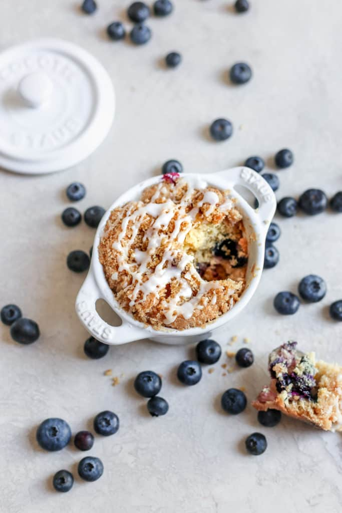 Triple berry coffee cake baked inside mini Staub cocottes with blueberries in the background.