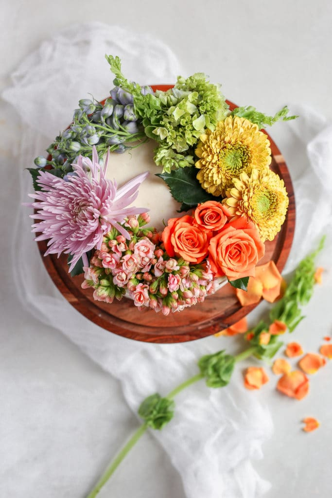 A white cake on a brown cake stand to show how to decorate a cake with flowers.