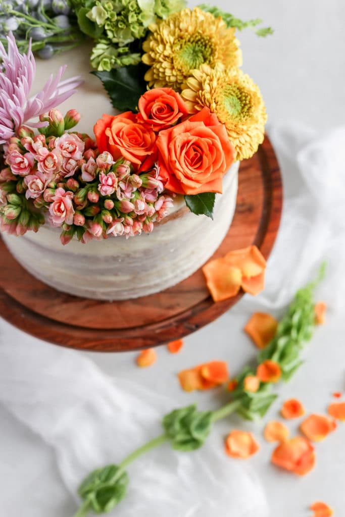 A white cake on a brown cake stand decorated with a rainbow of fresh flowers demonstrating how to decorate a cake with flowers