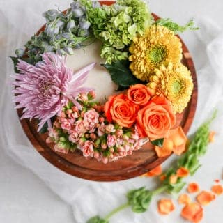 A white cake on a brown cake stand decorated with a rainbow of fresh flowers