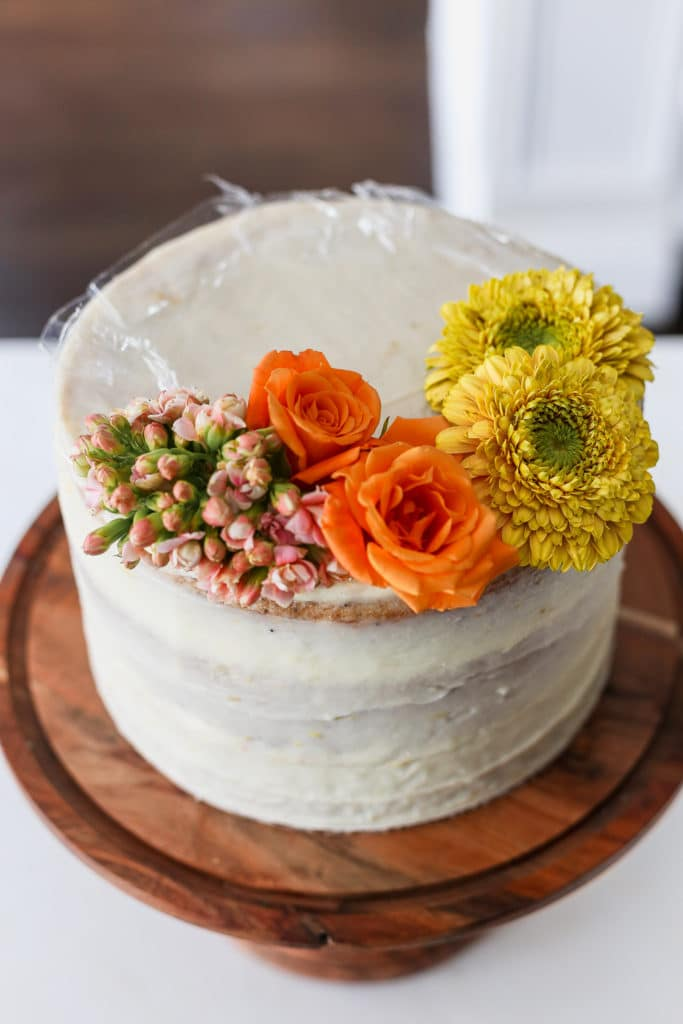 A white cake demonstrating how to decorate a cake with flowers.