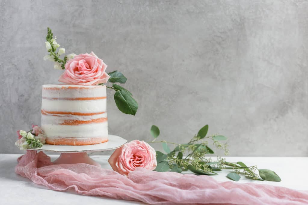 A naked cake decorated with pink roses on a cake stand with pink cheesecloth on a gray board