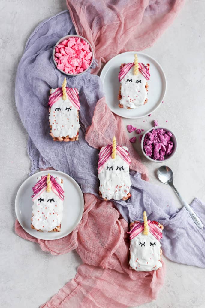 Cereal unicorn snack bars on a gray background with pink and purple cheesecloth.