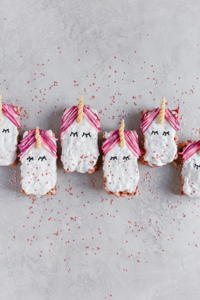 Cereal unicorn snack bars styled on a gray background with confetti pink hearts.
