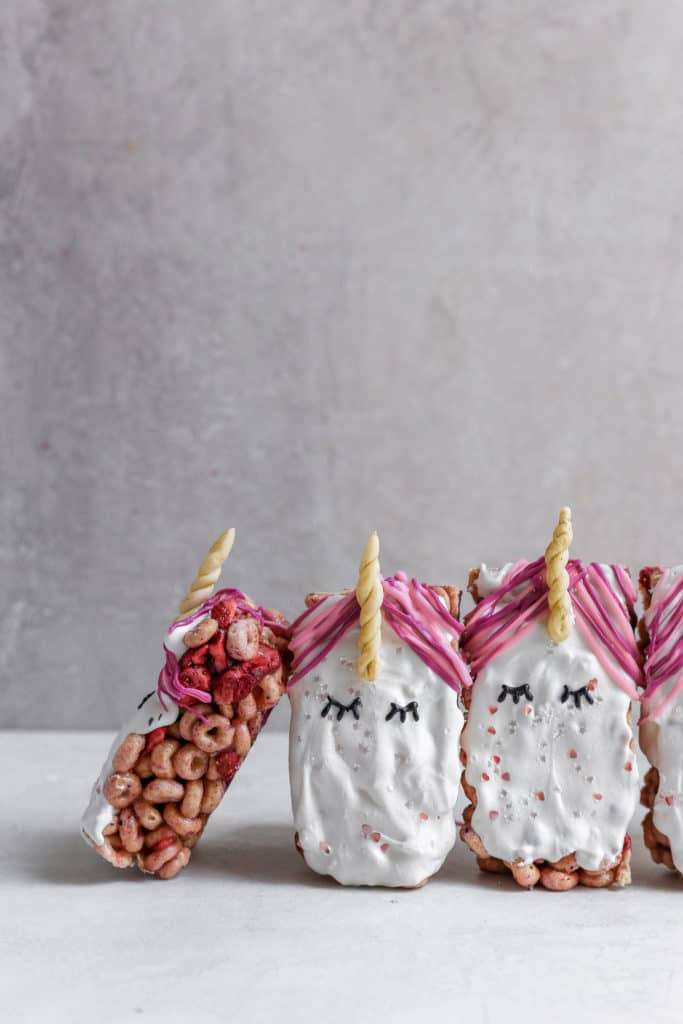 Cereal unicorn snack bars standing up on a gray background.