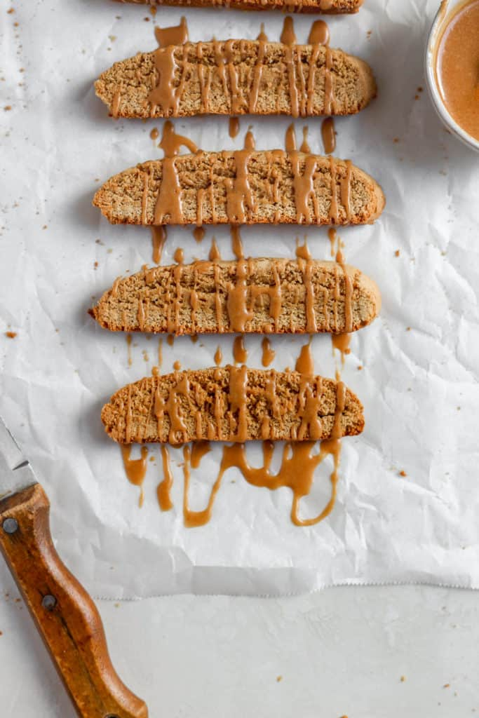 Fresh cookie butter biscotti drizzled with a cookie butter glaze on a white background.