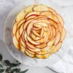 Sliced apples arranged on a cake to look like a giant rose.