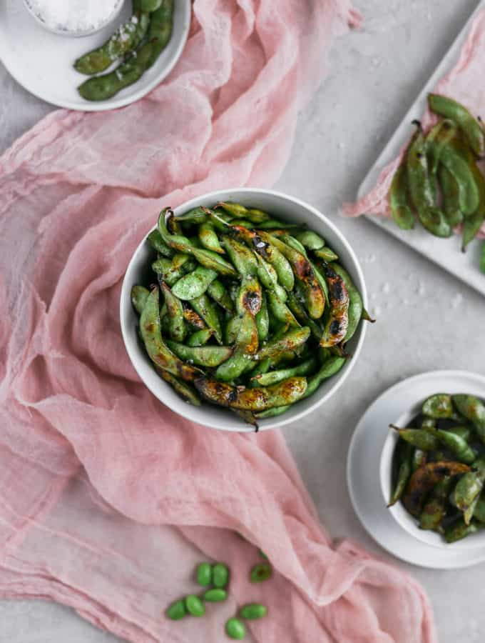 Blistered edamame with soy sauce and lime in a bowl styled with pink cheesecloth on a gray background.