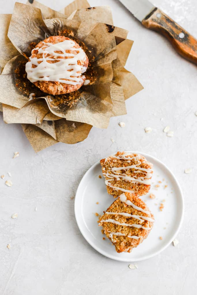Carrot cake muffin with cream cheese glaze styled on a gray background.