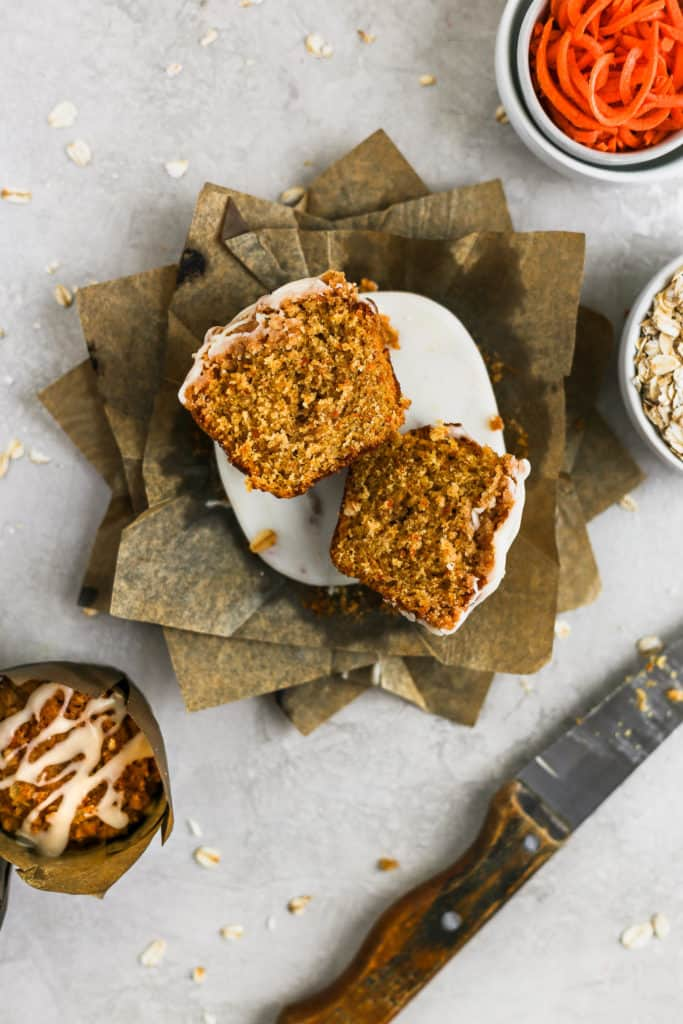 Carrot cake muffin with cream cheese glaze sliced in half styled on a gray background with oats in a bowl and a knife.