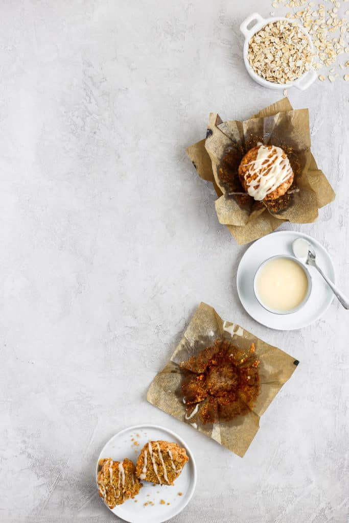 Carrot cake muffin with cream cheese glaze styled on a gray background with a lot of negative space.