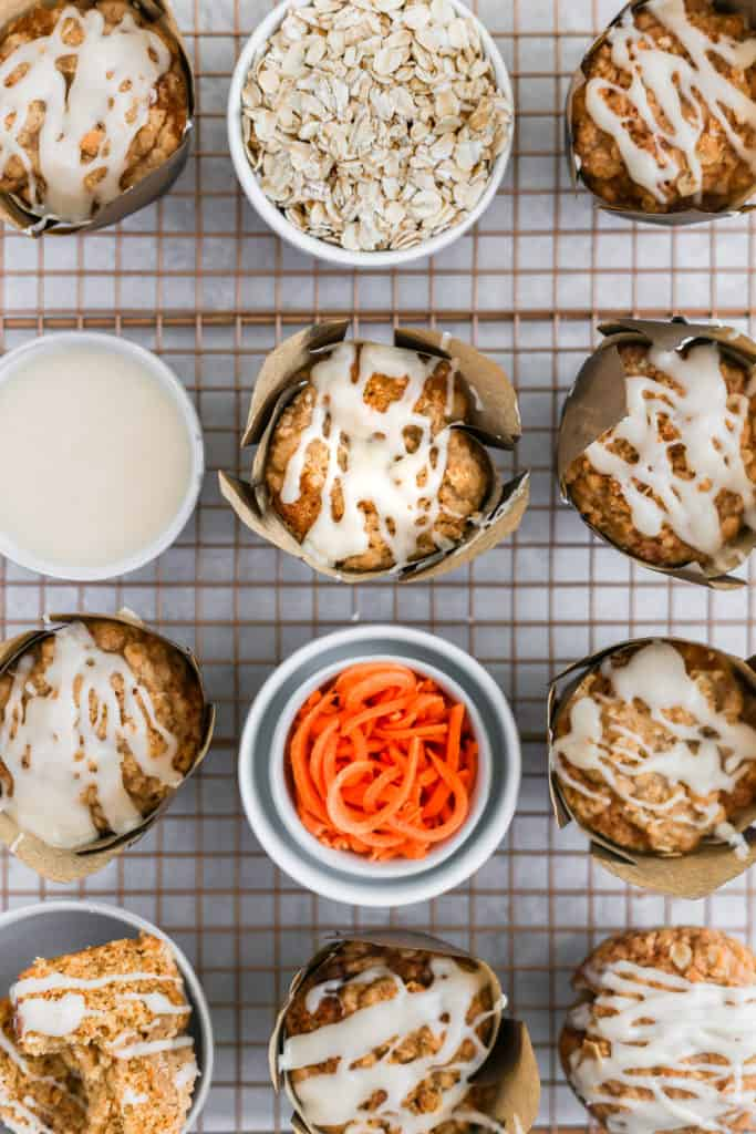 Carrot cake muffins with cream cheese glaze styled with bowls of ingredients on a cooling rack.