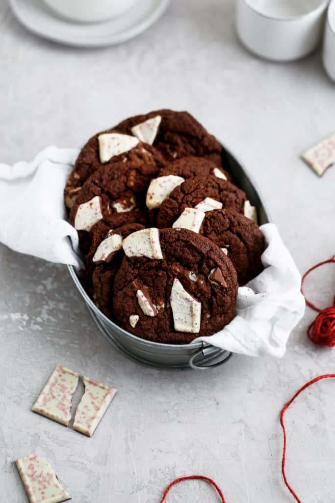Double chocolate peppermint cookies sitting in a tin on a grey food photography background.