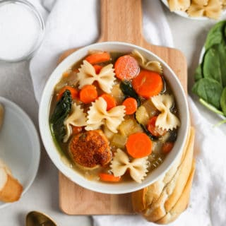 Easy Italian wedding soup with a turkey meatball in a white bowl styled on a cutting board. Frosting and Fettuccine