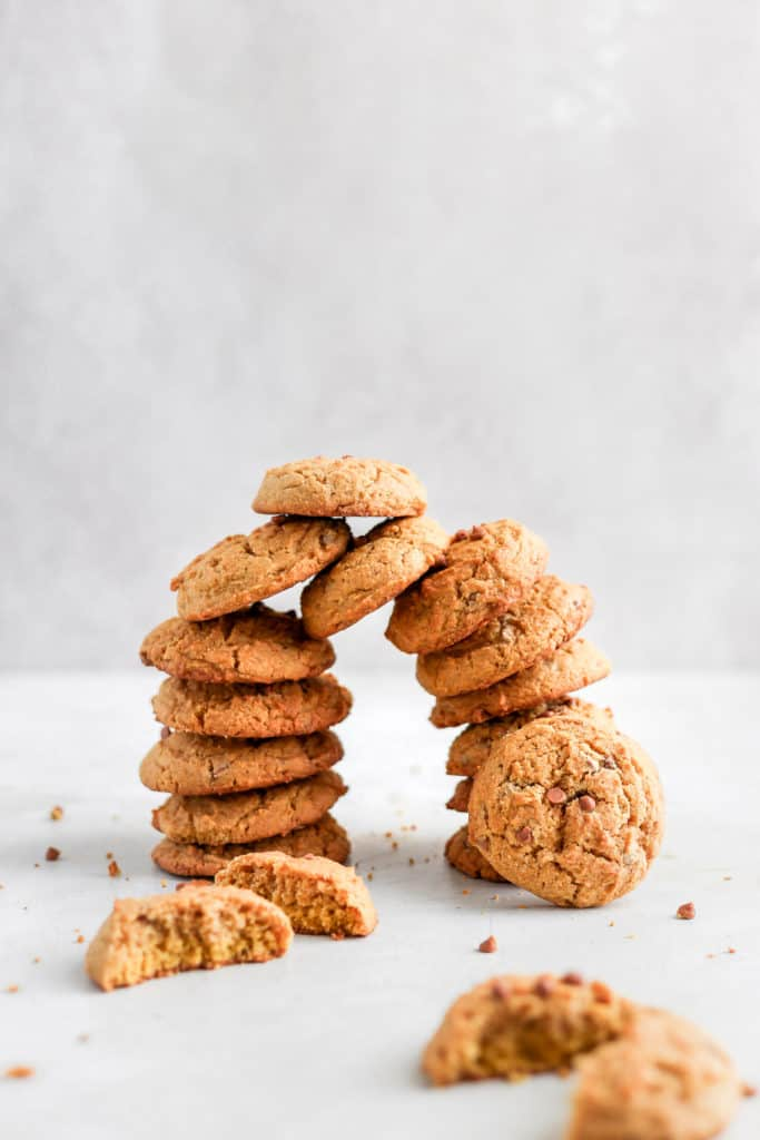Chewy pumpkin maple cookies stacked on top of each other on a grey background.