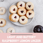Raspberry lemon linzer cookies displayed on a small plate on a grey background.