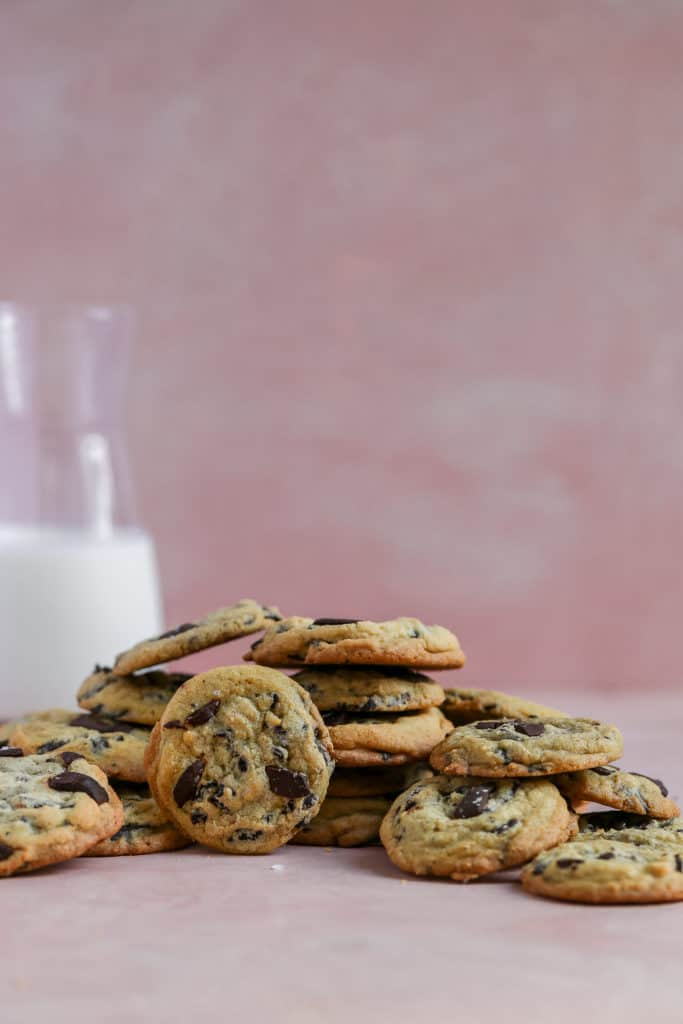 Salted caramel chocolate chip cookies displayed on a pink background.