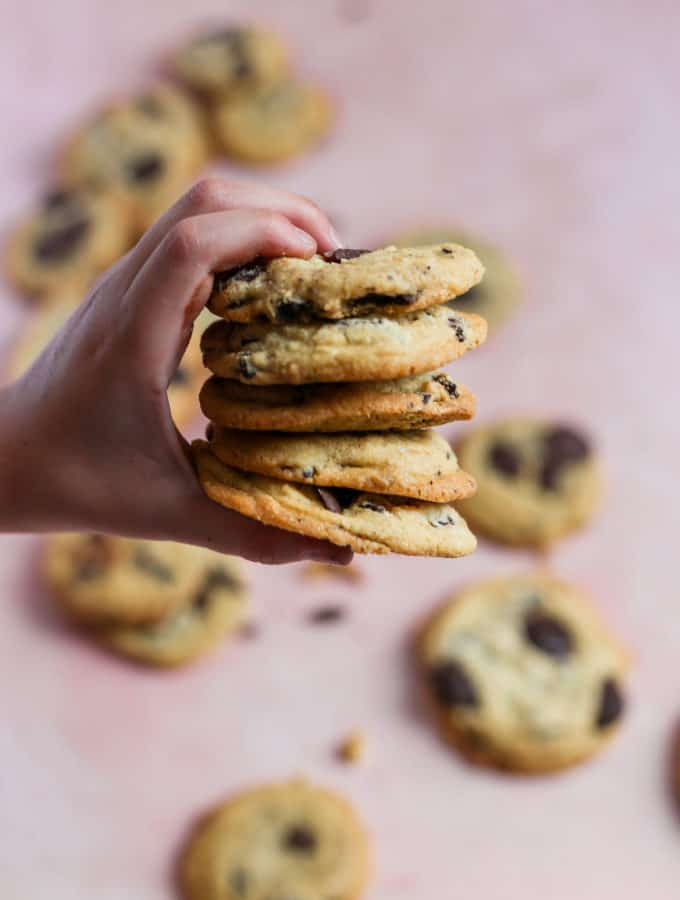 A child holding a stack of salted caramel chocolate chip cookies.
