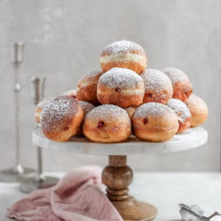 Chanukah jelly donuts arranged on a cake stand with candlestick in the background.